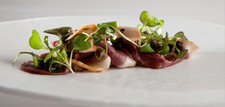Carpaccio de magret de pato con virutas de foie gras y vinagreta de trufas